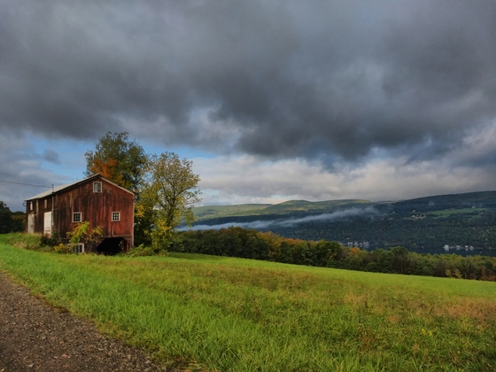 A barn and Keuka with mist on the hill